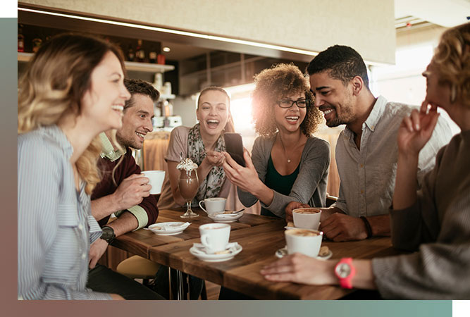 Group of six friends having coffee and laughing